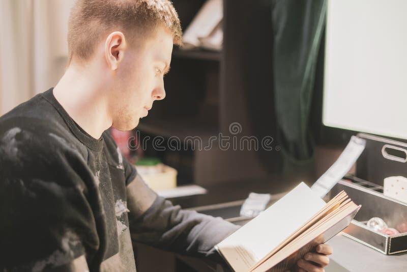 Młody człowiek czyta nauki książkę w warsztatowym miejscu f zdjęcie stock