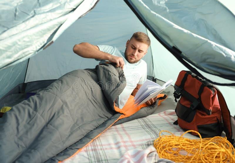 Młody człowiek czytelnicza książka w sypialnej torbie obraz stock