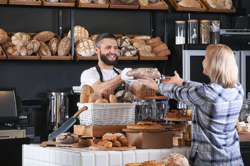 Młody człowiek daje świeżemu chlebowi kobieta w piekarni zdjęcia royalty free