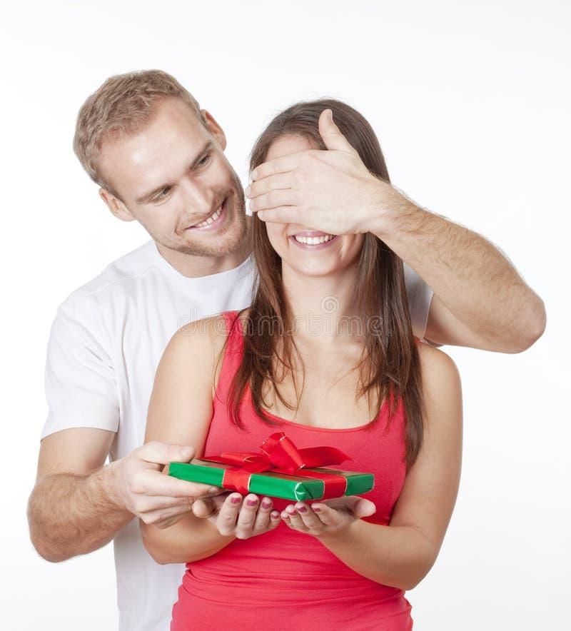 Młody człowiek daje niespodziance teraźniejszej jego dziewczyna obrazy royalty free