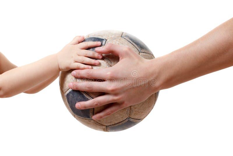 Młody człowiek daje starego piłki nożnej piłki dzieciaka, odosobnionego na bielu zdjęcia royalty free