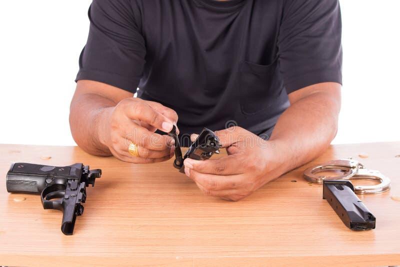 Młody człowiek demontujący pistolet na stole fotografia royalty free