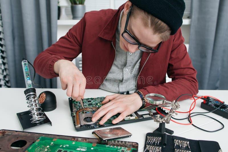 Młody człowiek demontuje komputerową płytę główną zdjęcia royalty free
