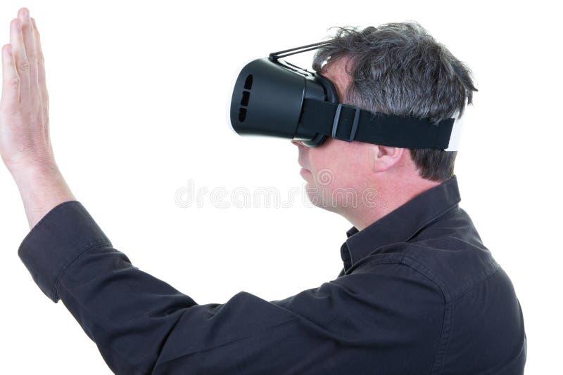Młody człowiek dotyka imaginacyjnego interfejs indoors z VR szkłami obrazy stock