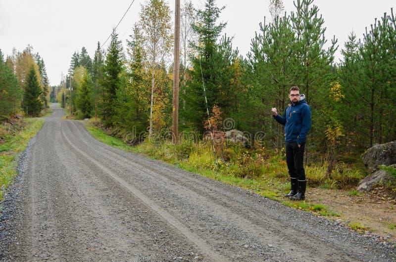 Młody człowiek hitchhiking na finnish wiejskiej drodze blisko drewien fotografia stock