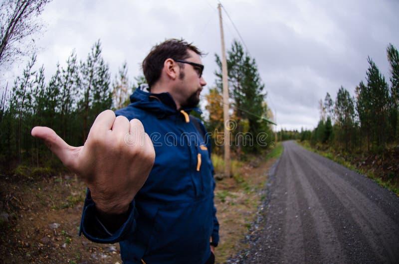 Młody człowiek hitchhiking na finnish wiejskiej drodze blisko drewien zdjęcia stock