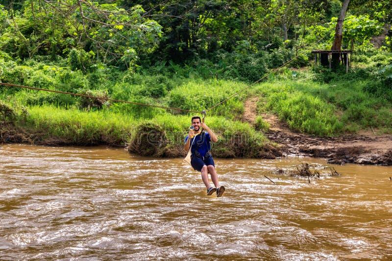 Młody człowiek iść przez rzeki na zamek błyskawiczny linii w Chiang Mai w Tajlandzkim zdjęcie royalty free