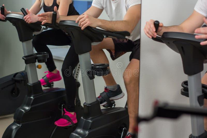 Młody człowiek i kobieta jechać na rowerze w gym, ćwiczy nogi robi cardio treningu kolarstwa rowerom zdjęcia royalty free