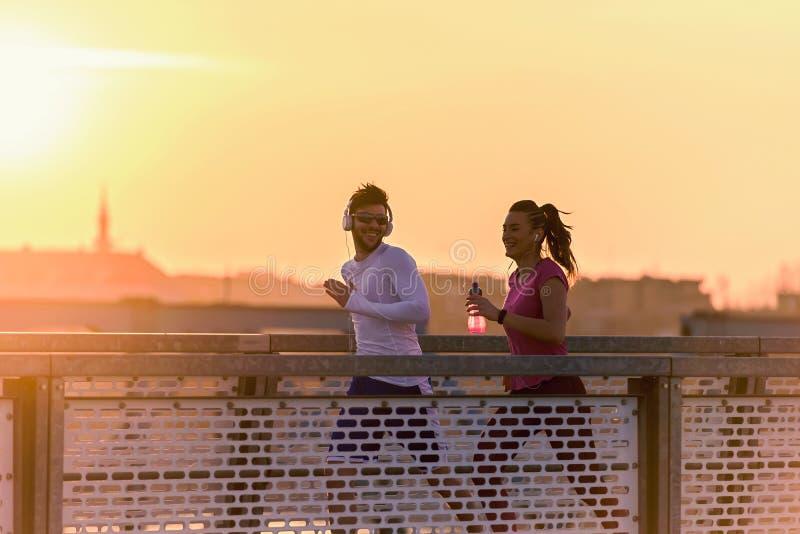Młody człowiek i kobieta jogging wpólnie nad mostem w wschód słońca lub zmierzchu zdjęcie royalty free