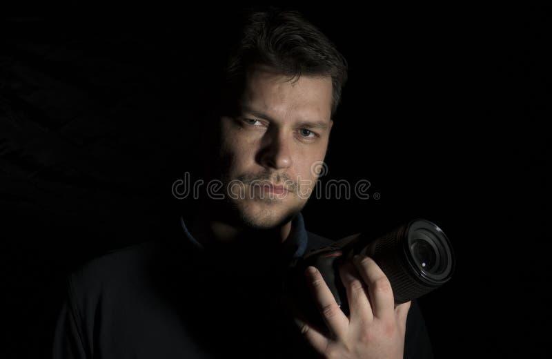 Młody człowiek jako fotografa portret odizolowywający na czerni zdjęcie royalty free