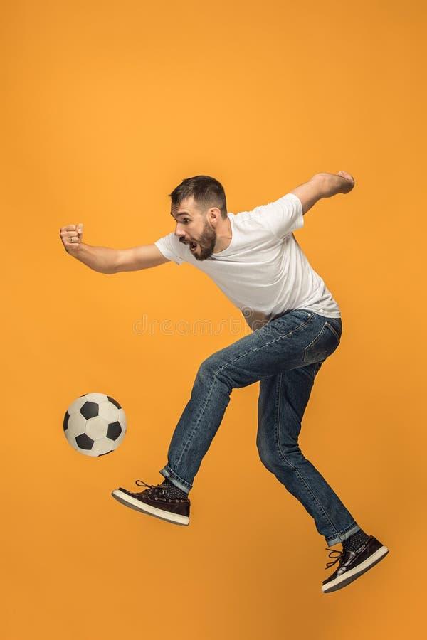 Młody człowiek jako piłka nożna gracz futbolu kopie piłkę przy studiiem zdjęcia stock
