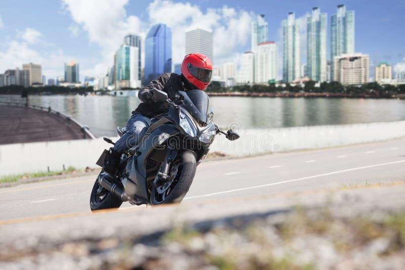 Młody człowiek jedzie dużego roweru motocykl na miasto drodze przeciw miastowemu zdjęcie stock