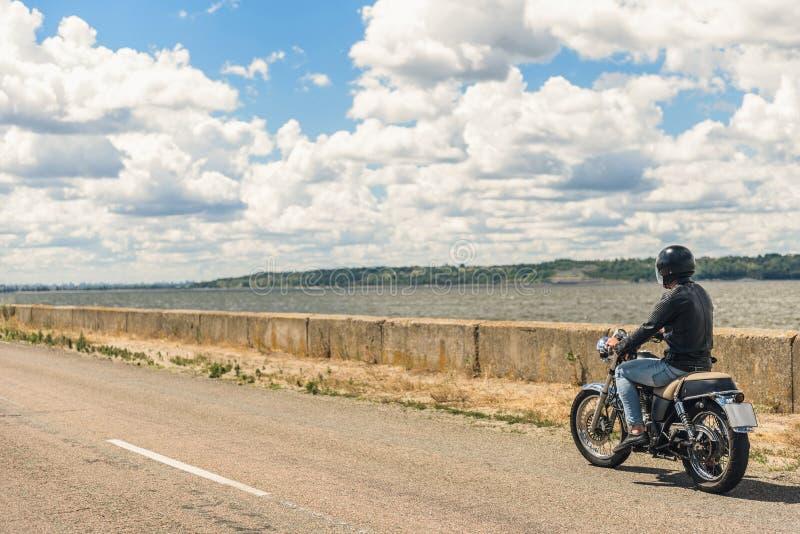 Młody człowiek jedzie jego motocykl na otwartej drodze zdjęcia stock