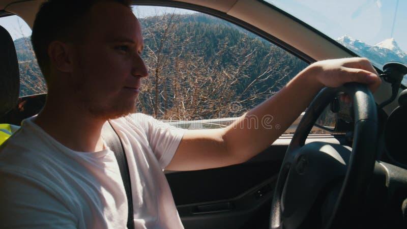 Młody człowiek jedzie samochód dolomity - widok na górach od okno - zdjęcie stock