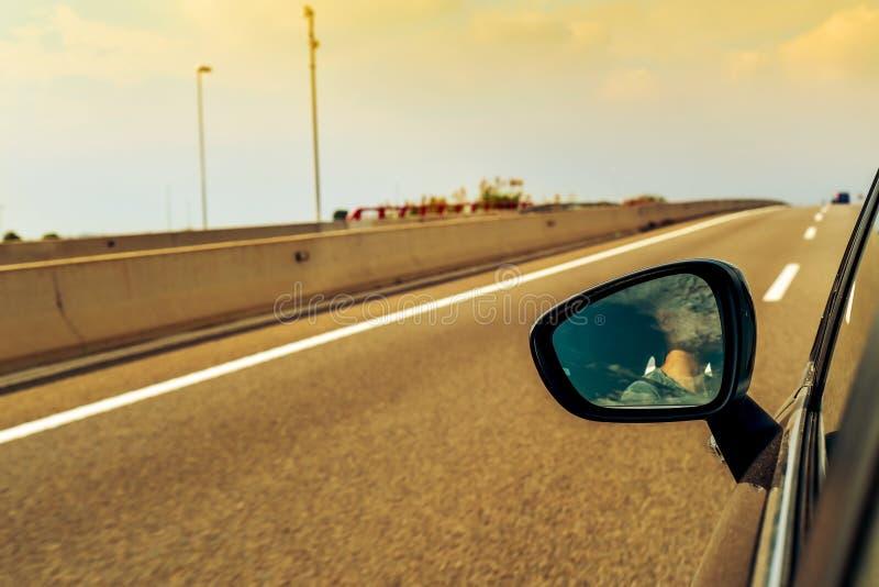 Młody człowiek jedzie samochód odbijał w skrzydłowym lustrze obrazy stock