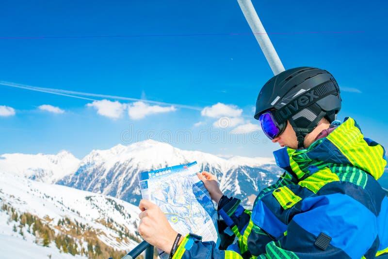 Młody człowiek jedzie w górę narciarskiego dźwignięcia bada mapę ośrodek narciarski obrazy royalty free