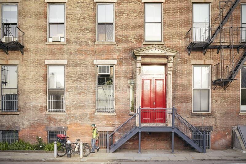Młody człowiek jego rowerem przed typowym Nowy Jork budynkiem mieszkaniowym obraz royalty free