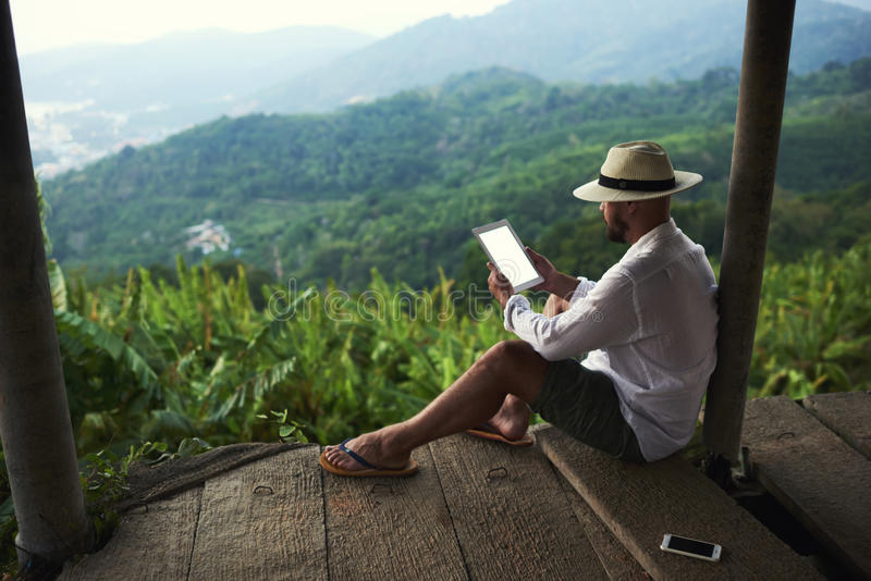 Młody człowiek jest czytelniczym pieniężnym wiadomością na cyfrowej pastylce podczas jego wycieczki w Tajlandia zdjęcie stock