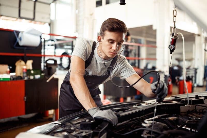 Młody człowiek jest ruchliwie z sprawdzać samochodu silnika: samochodu utrzymanie i naprawa zdjęcie royalty free