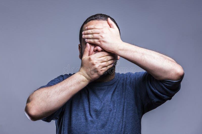 Młody człowiek jest ubranym błękitnego koszulowego nakrycia usta z rękami i oczy, zdziwiony i szokujący Chować emocję obrazy royalty free