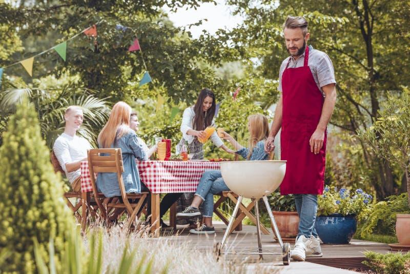 Młody człowiek jest ubranym Burgundy fartucha kucharstwo na białym grillu P zdjęcia stock