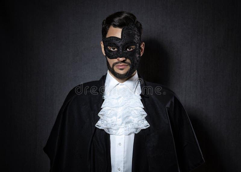 Młody człowiek jest ubranym ciemną maskę, ubierającą w fantomu opery spojrzenie zdjęcia royalty free