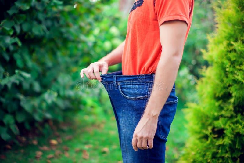 Młody człowiek jest ubranym dużych luźnych cajgi - ciężar straty pojęcie obrazy stock