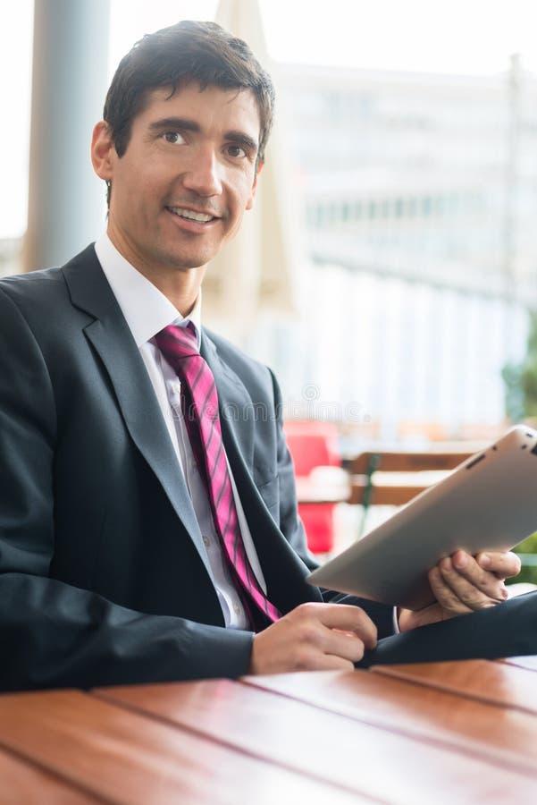 Młody człowiek jest ubranym garnitur podczas gdy używać pastylka peceta podczas b zdjęcia stock