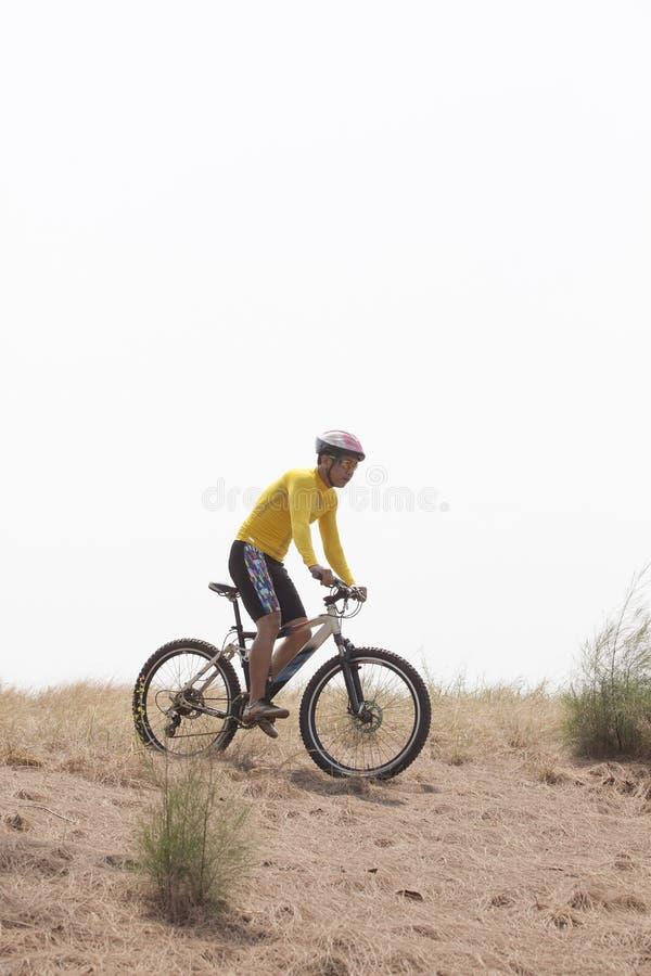 Młody człowiek jest ubranym jeźdza kostiumu roweru górskiego jeździeckiego MBT na zakurzonym r zdjęcie royalty free