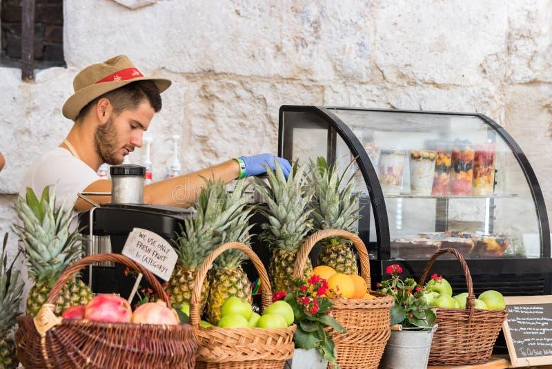 Młody człowiek jest ubranym kapelusz gniesie owoc robić świeżemu sokowi w ulicznym rynku w rozłamu błękitne rękawiczki i, Chorwac zdjęcia stock