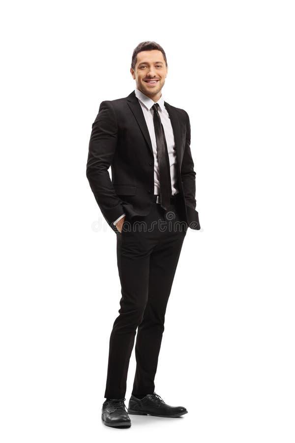 Młody człowiek jest ubranym nowożytnych czarnych ono uśmiecha się i kostium zdjęcia royalty free