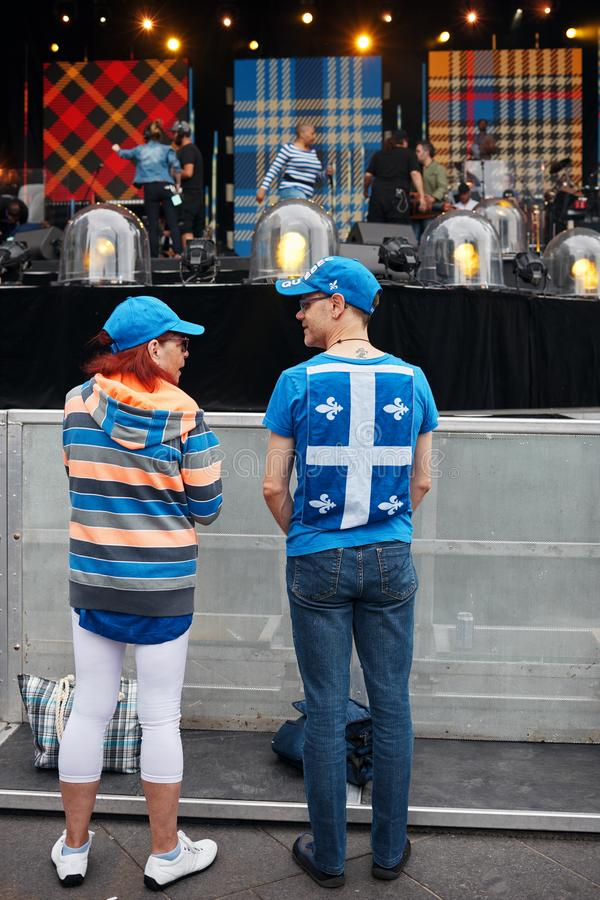 Młody człowiek jest ubranym Quebec flagę na jego przy Montreal festiwalem jazzowym w Kanada plecy gawędzenie z kobietą przed scen obraz stock