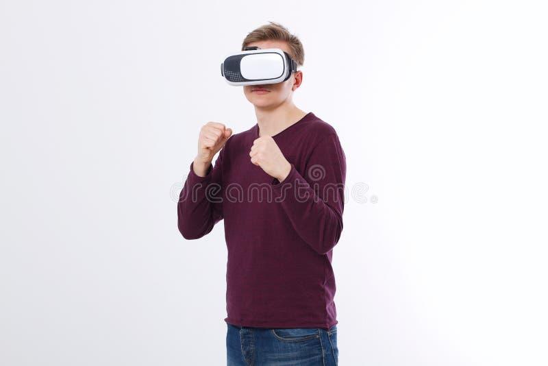 Młody człowiek jest ubranym rzeczywistość wirtualna gogle odizolowywających na białym tle VR szkieł technologii słuchawki i bokse obrazy royalty free