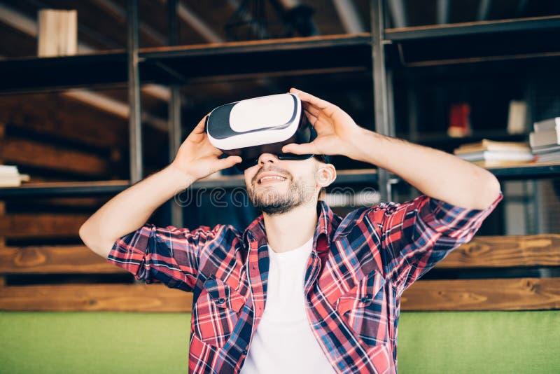 młody człowiek jest ubranym rzeczywistość wirtualna gogle w nowożytnym coworking studiu zdjęcia royalty free