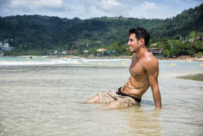 Młody człowiek kłaść na plaży oceanem obraz royalty free