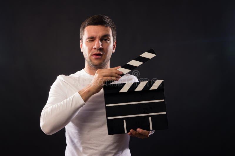 Młody człowiek Kaukaski pojawienie trzyma clapperboard Pora zdjęcie stock