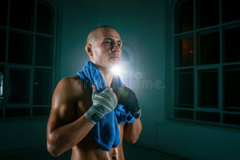 Młody człowiek kickboxing na czarnym tle zdjęcia stock
