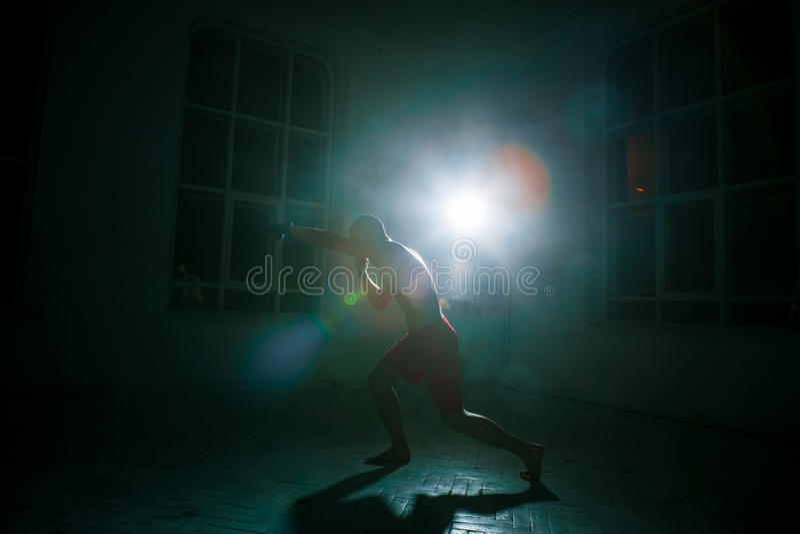 Młody człowiek kickboxing na czarnym tle obraz royalty free
