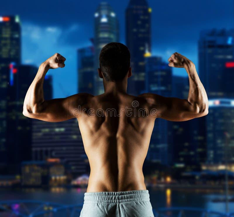 Młody człowiek lub bodybuilder pokazuje bicepsy zdjęcia stock