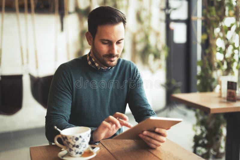 Młody człowiek lub studencki używa pastylka komputer w kawiarni obraz stock