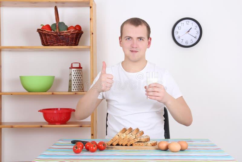 Młody człowiek ma śniadanie w kuchni zdjęcia stock