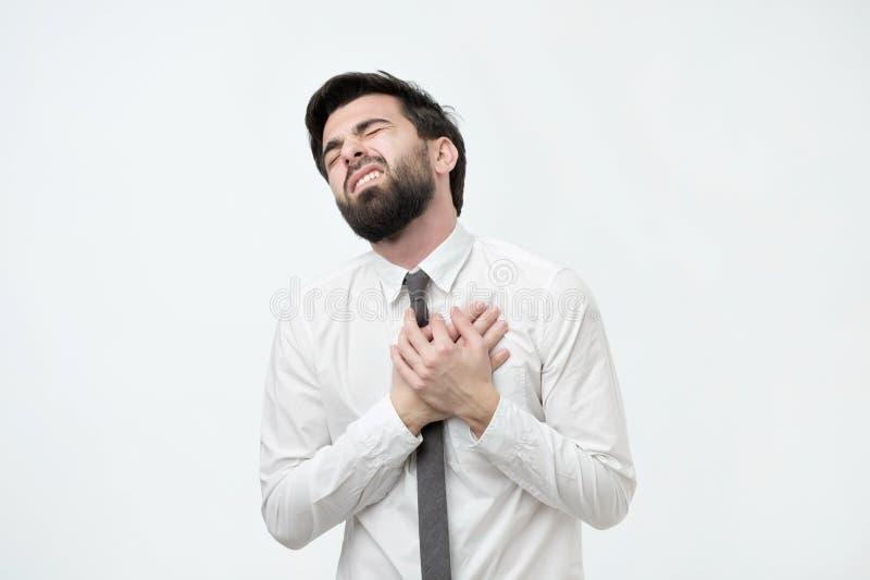 Młody człowiek ma ataka serca na białym tle fotografia stock