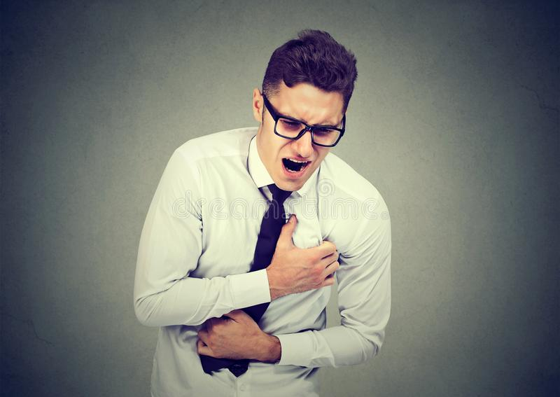Młody człowiek ma klatka piersiowa ból, atak serca zdjęcie stock
