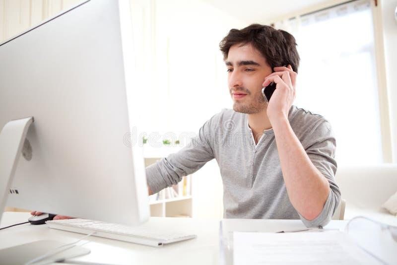 Młody człowiek ma wezwanie przed komputerem fotografia royalty free