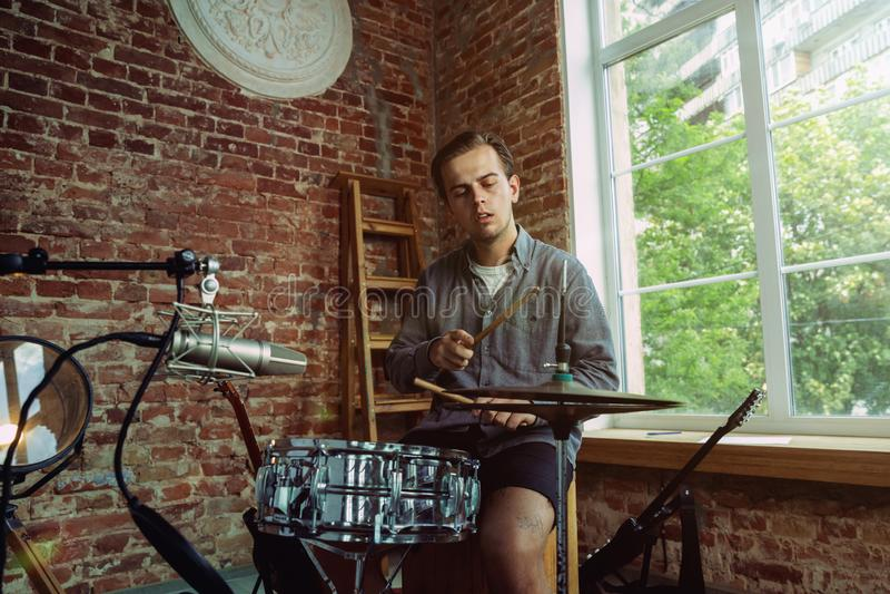 Młody człowiek magnetofonowa muzyka, bawić się bębeny i śpiew w domu zdjęcia royalty free