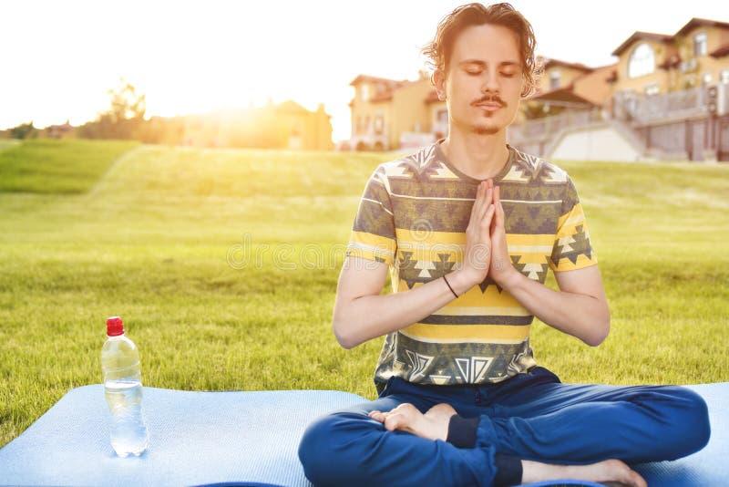 Młody człowiek medytuje outdoors w parku, siedzący z oczami zamykającymi i jego wręcza wpólnie cieszyć się naturę, joga i medytac fotografia stock
