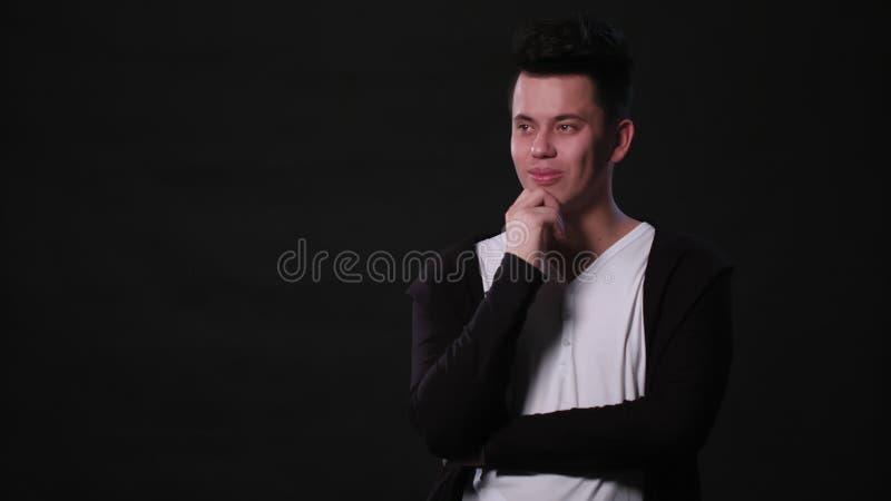 Młody człowiek mimicing przeciw czarnemu tłu obrazy stock