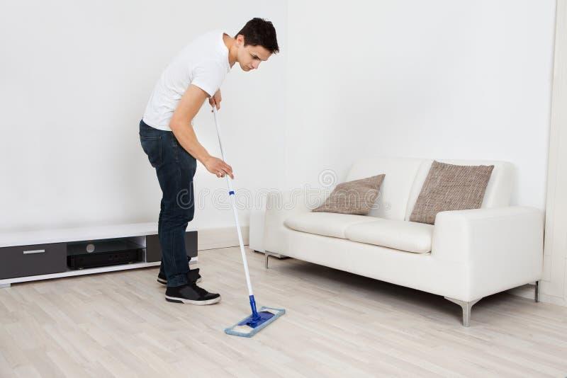 Młody Człowiek Mopping podłoga W Domu zdjęcia stock