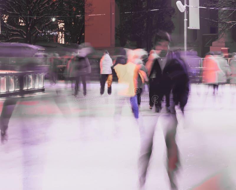 Młody człowiek na łyżwach przeciw tłu miasta łyżwiarski lodowisko w parku Wizerunku zamazywać i dwoisty skład fotografia royalty free