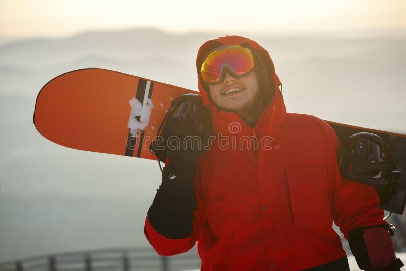 Młody człowiek na tle zmierzchu niebo z snowboard obraz royalty free